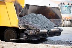 Paver seguido que coloca o pavimento fresco do asfalto durante o constru da estrada imagens de stock