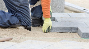 Paver working on knees Stock Photos