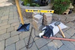 Pavers de pedra do tijolo com ferramentas de jardim Fotografia de Stock Royalty Free