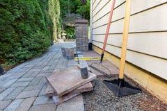 Pavers e ferramentas de pedra para ajardinar da casa da jarda lateral Imagem de Stock Royalty Free