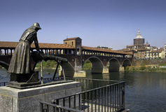 Pavia - Covered Bridge over the Ticino River. The statue of the laundress and the old bridge is a brick and stone arch bridge over the Ticino River in Pavia Stock Image