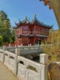 Pavilhão do chá na cor vermelha tradicional com feixes de telhado azuis no jardim chinês no parque Pairi Daiza dos animais selvag fotos de stock royalty free