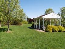 Pavilhão do piquenique por um gramado verde e por árvores Foto de Stock Royalty Free