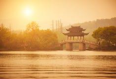 Pavilhão e ponte do estilo tradicional no lago no por do sol, Hangzhou XiHu, China Fotos de Stock Royalty Free