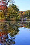 Pavilion with Autumn Reflections. A wooden pavilion surrounded by reflections of autumn colors on the water Stock Images