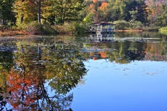 Pavilion with Autumn Reflections. A wooden pavilion surrounded by reflections of autumn colors on the water Stock Photos
