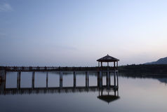 Pavilion and footbridge in the morning. Waterside tranquil scenery in remote county Royalty Free Stock Image