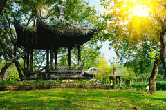 Pavilion of old Chinese style in public park with sun lighting flare effect. Royalty Free Stock Image
