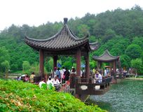 A pavilion over the lake with tourists walking through Stock Photo