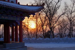 A pavilion and sunset. At the edge of road,there is a pavilion under the white snow,and the sunlight fell over it thorugh some trees . Liaoyuan, Jilin  Province Royalty Free Stock Image