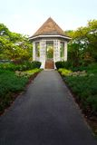 Pavilion in tropical garden with herb border lands stock photo