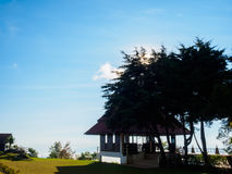 A pavilion under green trees and blue sky, concept for background texture. Stock Image