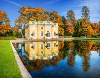 Pavilion  `Upper Bath` in Catherine Park in Tsarskoye Selo. Pavilion `Upper Bath` in Catherine Park in Tsarskoye Selo and a mirror pond on a clear sunny autumn Royalty Free Stock Photos