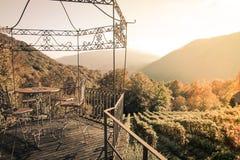 Paviljong i vineardsna med tabellen och stolar under solnedgång Arkivbilder