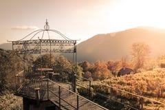 Paviljong i vineardsna med tabellen och stolar under solnedgång Arkivfoto