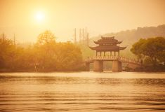 Paviljong och bro för traditionell stil på XiHu sjön på solnedgången, Hangzhou, Kina Royaltyfria Foton