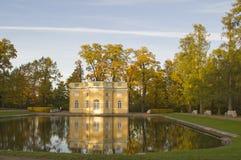 Paviljong som reflekterar i dammet in i Tsarskoe Selo nära St Petersburg Arkivfoto