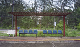 Paviljong som vilar av drevpassagerare på en trottoar på järnvägsstationen, Thailand, tillfogad ljus effekt, selektiv fokus, filt Royaltyfri Bild