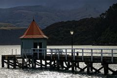 Pavillion on the jetty. A Pavillion on the jetty in Akaroa harbour, New Zealand. A dark and moody scene with the sun reflecting off the sea stock photography