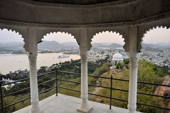 Pavillon with Udaipur city palace at Pichola lake. A view of a pavillon in front of Udaipur city palace at the shores of Pichola lake in Udaipur, Rajasthan Stock Photography