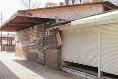 Pavillons commerciaux fermés et metallosayding embarqué construisant un café de trottoir sur la rue abandonnée de bord de la mer Photographie stock libre de droits