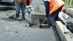 Pavimentación del camino Trabajadores que ponen el asfalto de masilla de piedra durante la calle que repara trabajos almacen de metraje de vídeo