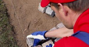 Pavimentación del guijarro - trabajador que instala las pavimentadoras de piedra del granito almacen de video