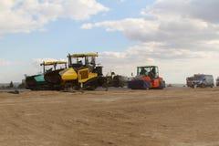 Pavimentadoras seguidas que ponen el pavimento fresco del asfalto en una pista como parte del plan de expansión del aeropuerto in Foto de archivo libre de regalías