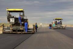 Pavimentadoras seguidas que ponen el pavimento fresco del asfalto en una pista como parte del plan de expansión del aeropuerto in Foto de archivo