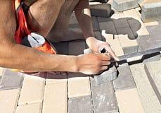 Pavimentando telhas em um terraço com uma régua e medição Imagens de Stock Royalty Free