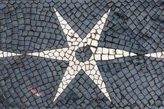 Pavimentazione del ciottolo di Lisbona nelle progettazioni bianche nere della stella fotografia stock libera da diritti