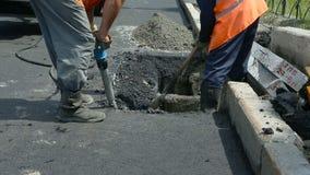 Pavimentazione della strada Lavoratori che pongono il mastice asfaltico di pietra durante la via che ripara gli impianti stock footage