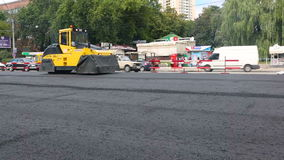 Pavimentazione della strada Lavoratori che pongono il mastice asfaltico di pietra durante la via che ripara gli impianti video d archivio