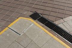 Pavimentazione di pietra con la rete fognaria di griglia del metallo Immagini Stock Libere da Diritti