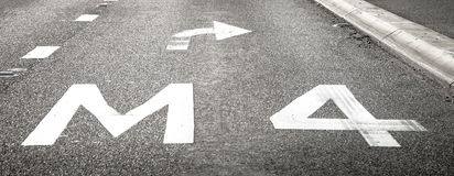 Pavimentazione di strada che segna M4 e freccia con svolta a destra Immagine Stock Libera da Diritti