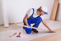Pavimentazione maschio del laminato del lavoratore Fotografie Stock