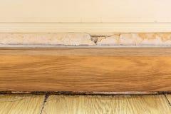 Pavimenti i modanature e dipinga il gonfiamento di colore sulla vecchia parete bianca Fotografie Stock Libere da Diritti