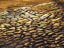 Pavimento antiguo: pavimentando bloques se hacen de los adoquines viejos de diversos tamaños, dispuestos en filas, en el sol el c Imagen de archivo