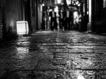 Pavimento bagnato con la gente di affari nel fondo fotografia stock