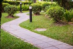 Pavimento da passagem do tijolo na passagem do jardim através do campo de grama com iluminação da lâmpada na terra ao lado Fotografia de Stock