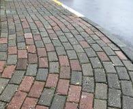 Pavimento de adoquín curvado con la calle Fotos de archivo