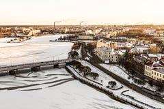 Pavimento de camino a lo largo del terraplén de la ciudad vieja de Vyborg de las fachadas nevadas de la bahía en el fondo del cie imagen de archivo libre de regalías