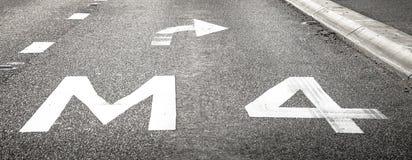 Pavimento de camino que marca M4 y la flecha de giro a la derecha Imagen de archivo libre de regalías