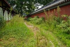 Pavimento de la losa entre el edificio envejecido y el recinto rojo adentro nosotros imagen de archivo