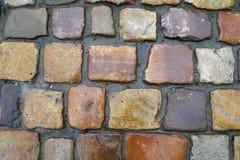 Pavimento de pedra, pedras da cor marrom e amarela do formulário quadrado, fundo do pavimento da pedra Imagem de Stock Royalty Free
