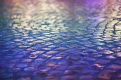 Pavimento de piedra del adoquín - reflexión en noche urbana. Acera azul mojada Fotos de archivo