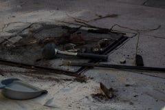 Pavimento de piedra gris al aire libre de la calle, con las herramientas colocadas hacia fuera y los escombros, que se ha trabaja fotos de archivo