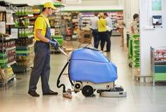 Pavimento del deposito di pulizia del lavoratore con la macchina Fotografie Stock Libere da Diritti