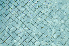 Pavimento della piscina con acqua blu-chiaro e la griglia nera in mezzo Immagini Stock Libere da Diritti