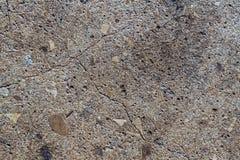 Pavimento di calcestruzzo incrinato con la fine dell'interno delle rocce su immagine stock